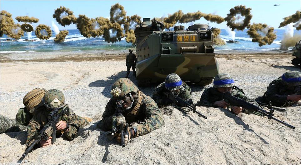 Fuzileiros navais dos EUA à esquerda e fuzileiros navais da República da Coreia à direita com faixas azuis, em Pohang, Coreia do Sul.