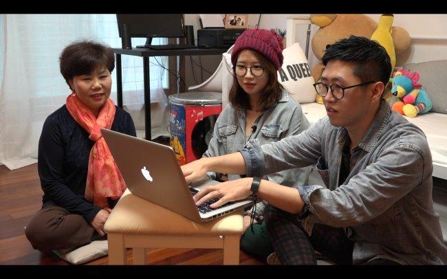 """Jeon Je-Woo (à direita) e sua esposa Park Mi-Young (centro) apresentam seus planos para a mãe de Mi-Young, no documentário """"One Way Ticket"""" de Do You-Jin."""