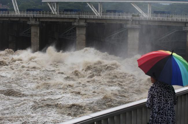 Um Cidadão Observa A Repressa Paldang Despejar Cerca De 3.409 Toneladas De Água Por Segundo Após Ser Atingida Pela Chuva Torrencial Em Hanam, Província De Gyeonggi, Na Terça-Feira. (Yonhap)