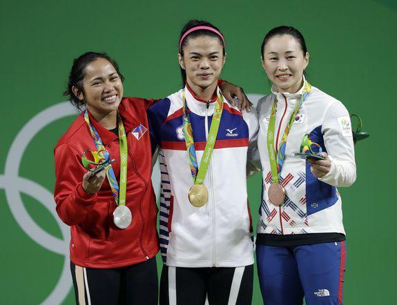 Yoon Jin-Hee com as atletas de Taipei e Filipinas após receberem as medalhas olímpicas. Foto: Mike Groll/AP