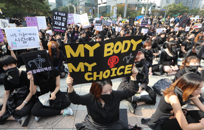 """Manifestantes segurando cartazes durante o protesto. """"Meu corpo, minhas escolhas"""", frase parecida com a brasileira """"Meu corpo, minhas regras"""". Fonte: Yonhap"""