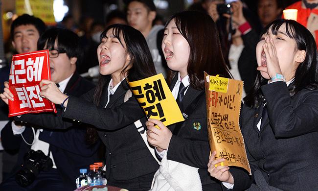 """Estudantes gritam """"Gun-Hye Park! Renuncie!,"""" enquanto seguram cartazes com a mesma mensagem. / Yonhap"""