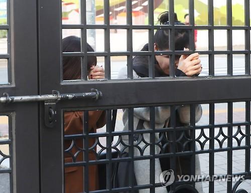 Pais fazem orações fora do portão de uma escola secundária de meninas em Suwon, ao sul de Seul, para enviar bênçãos aos filhos que estão prestando o exame. Foto: Yonhap