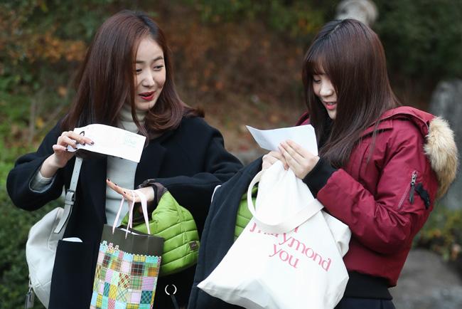SinB do GFriend, à esquerda, e Umji a verificar os seus bilhetes de entrada do teste antes de entrar na Dongil Girls 'High School para fazer o teste.