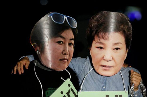 Manifestantes ridicularizam Park Geun-hye e Choi Soon-sil.