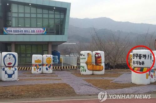 """Algumas estruturas foram colocadas próximas a um centro comunitário em Cheongyang. Um aviso, circulado de vermelho, diz """"crescimento populacional"""" e """"Vila rural rica"""", 7 de Janeiro, 2017. (Yonhap)"""