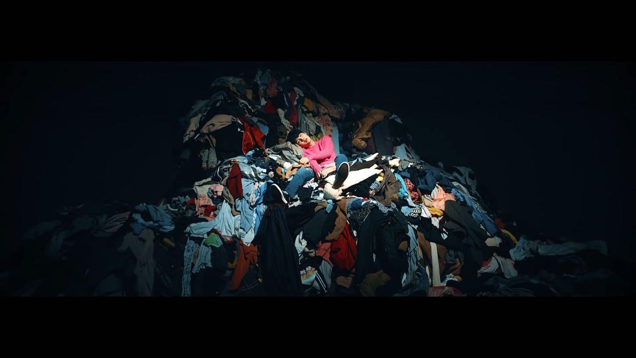 Suga e a pilha de roupas, no escuro, sozinho.