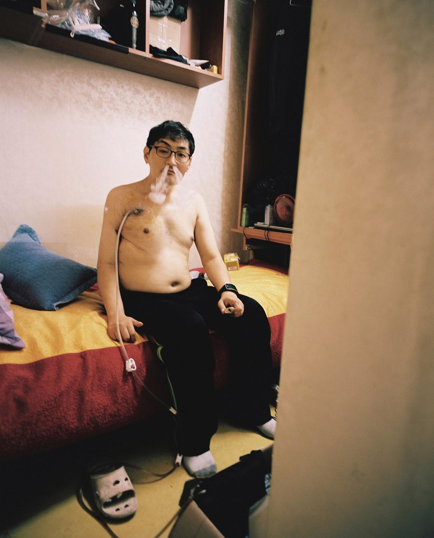 Este homem foi ferido durante a Primeira Batalha de Yeonpyeong em 2002 e recebe um milhão de won por mês da pensão dos veteranos. Ele está usando tubos que ajudam a remover fluidos corporais e fumar cigarro eletrônico. Foto: Sim Kyu-dong.
