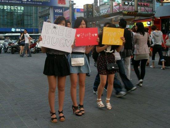 """Jovens distribuindo """"abraços gratuitos"""" nas ruas de Myeongdong, atividade que vem se tornando cada vez mais popular no país. Foto: koreabridge.net"""