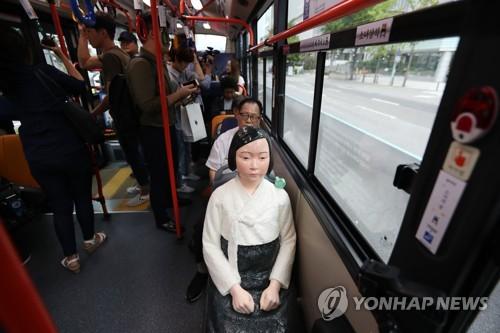 Estátua de mulher de conforto em ónibus durante o dia internacional das mulheres de conforto./ Yonhap News