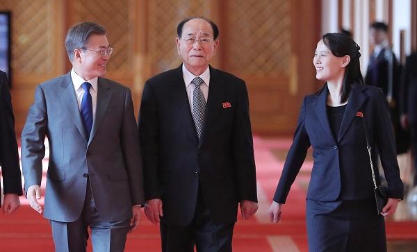 Presidente Moon Jae-in, na esquerda, conversa com Kim Yo-jong, na direita, a irmã mais nova do líder da Coreia do Norte, Kim Jong-un, enquanto caminham para a reunião na Blue house. Kim Yong-nam, Chefe de Estado nominal é visto no meio. (Via: YONHAP)