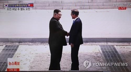 A imagem captada de uma transmissão televisiva mostra o presidente sul-coreano Moon Jae-in (à direita) e o líder norte-coreano Kim Jong-un apertando as mãos após atravessar a fronteira inter-coreana na Área de Segurança Conjunta da Panmunjom, onde se encontraram em 27 de abril , 2018, para a terceira reunião inter-coreana. Foto: Yonhap