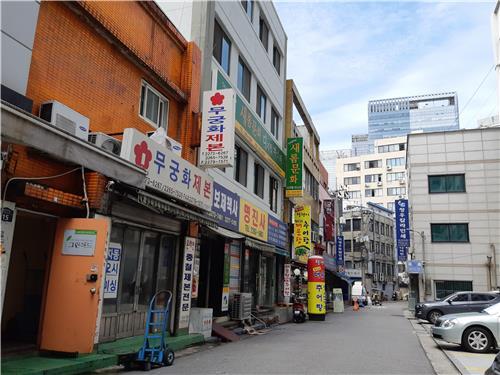 Foto tirada em julho de 2018, mostrando a localização da Cafeteria Soosunhwa, no quarto andar do prédio branco à esquerda. (Imagem: Yonhap)