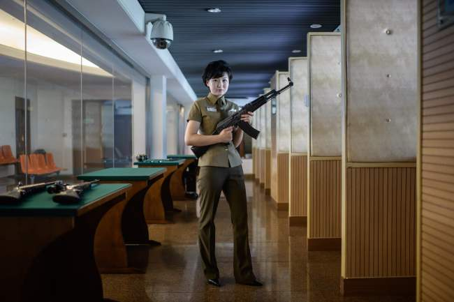 TOPSHOT - In a photo taken on July 29, 2018 instructor Kim Ju Yang (20) holds a North Korean-made assault rifle as she poses for a portrait at the Meari shooting range in Pyongyang. The Meari shooting range offers customers the opportunity to shoot a number of North Korean and foreign-made firearms, most of which have been modifed to fire .22 calibre ammunition costing one US dollar per round. / AFP PHOTO / Ed JONES/2018-08-01 18:23:37/