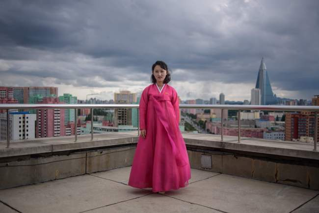 In a photo taken on June 16, 2018 tour guide Ju Hye Yon poses for a portrait on a viewing deck of the Arch of Triumph, before the city skyline of Pyongyang. / AFP PHOTO / Ed JONES/2018-07-31 15:20:18/