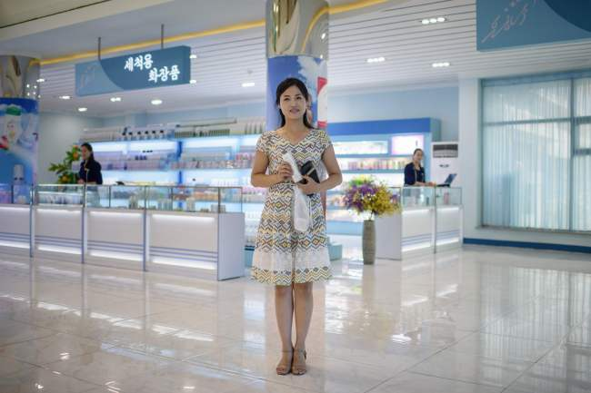 In a photo taken on July 28, 2018 shopper Pay Ok Hyang (24) poses for a portrait with her purchase in the shop of the Pyongyang Cosmetics Factory in Pyongyang. / AFP PHOTO / Ed JONES/2018-07-31 15:20:12/