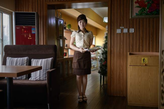 In a photo taken on July 28, 2018 Rim Ok Hyang (20) poses for a photo at a hamburger restaurant in Pyongyang. / AFP PHOTO / Ed JONES/2018-07-31 15:20:12/