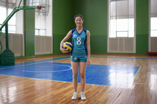 In a photo taken on July 26, 2018 volleyball player Ri Yun Sim (15) poses for a portrait in a gymnasium at the Children's Palace in Pyongyang. The Children's Palace is a vast afterschool activity complex where up to 5000 children attend various classes under a triumvirate of sports, arts, and science. The Palace is a regular fixture on tour group schedules. / AFP PHOTO / Ed JONES/2018-07-31 15:20:12/