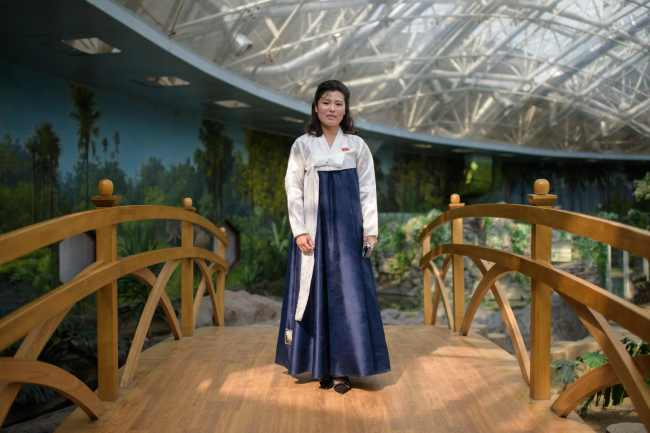 In a photo taken on July 29, 2018 tour guide Kim Song Hui (26) poses for a portrait at the reptile enclosure of the Central Zoo in Pyongyang. / AFP PHOTO / Ed JONES/2018-07-31 15:20:12/