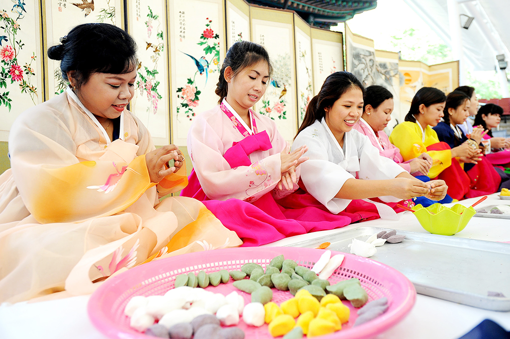 """As esposas estrangeiras aprendem a fazer o """"songpyeon,"""" (bolo de arroz no formato de meia-lua, tradicional do Chuseok) em um centro comunitário de Songpa-gu, Seul. Foto: Yonhap"""