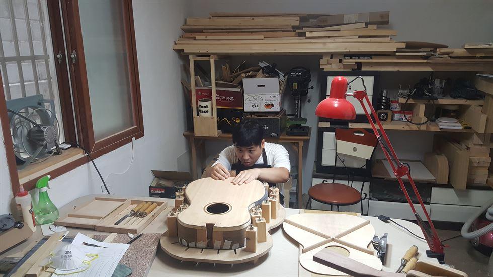 Joo Myung-geen encaixa peças de violão em sua oficina.