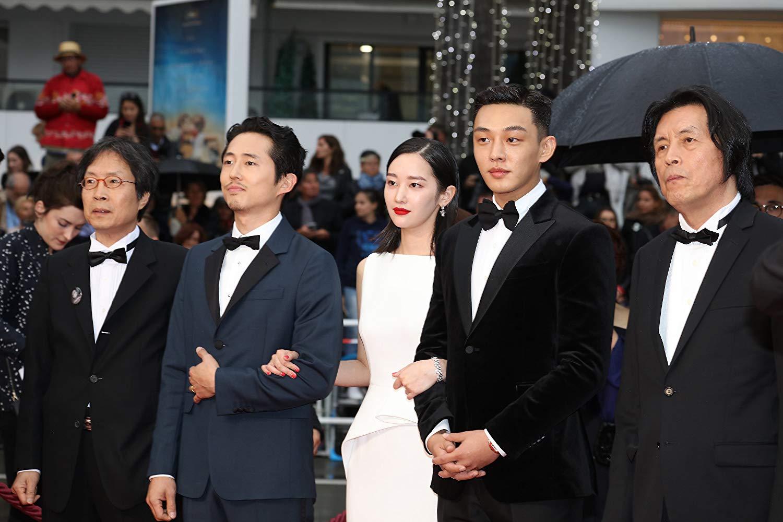 """Da esquerda para a direita o produtor Joon-dong Lee, os atores Steven Yeun, Jong-seo Jeon, Ah-In Yoo, e o diretor Chang-dong Lee comparecem ao Festival de Cannes para a exibição de """"Em Chamas"""". Foto: IMDb."""